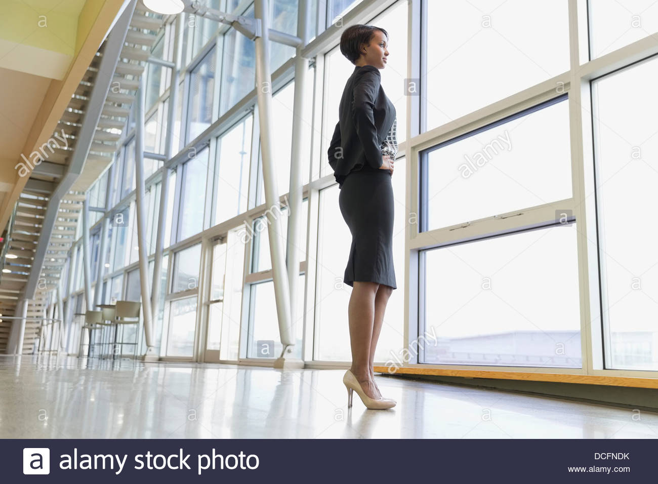 Full length businesswoman looking out window - Stock Image