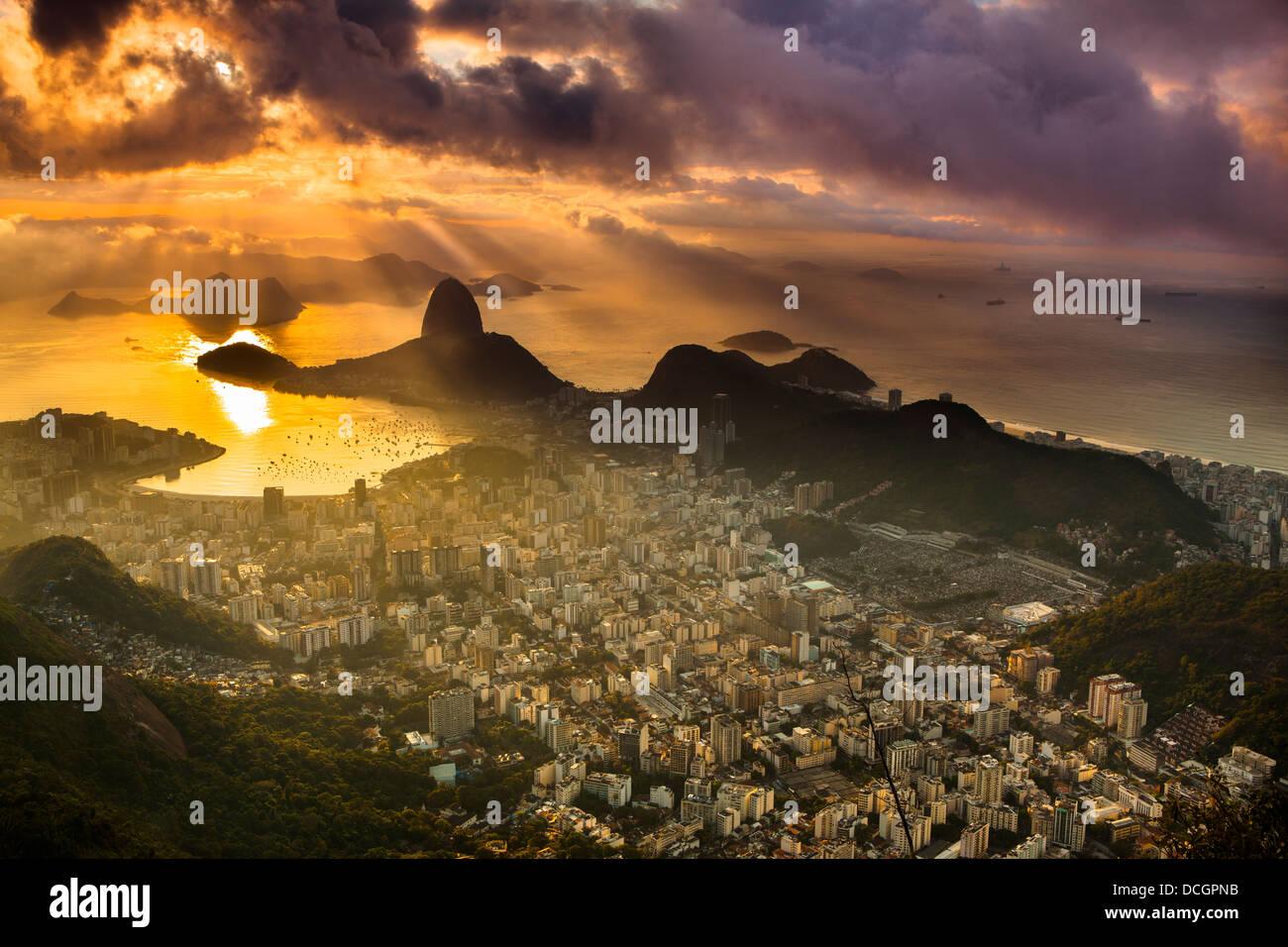 Rio de Janeiro cityscape, Brazil. Sugar Loaf, Botafogo beach and neighborhood seen from Corcovado at sunrise impressive - Stock Image