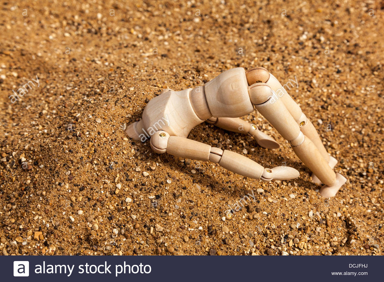 Denial - Mannequin with head buried in the sand Stock Photo