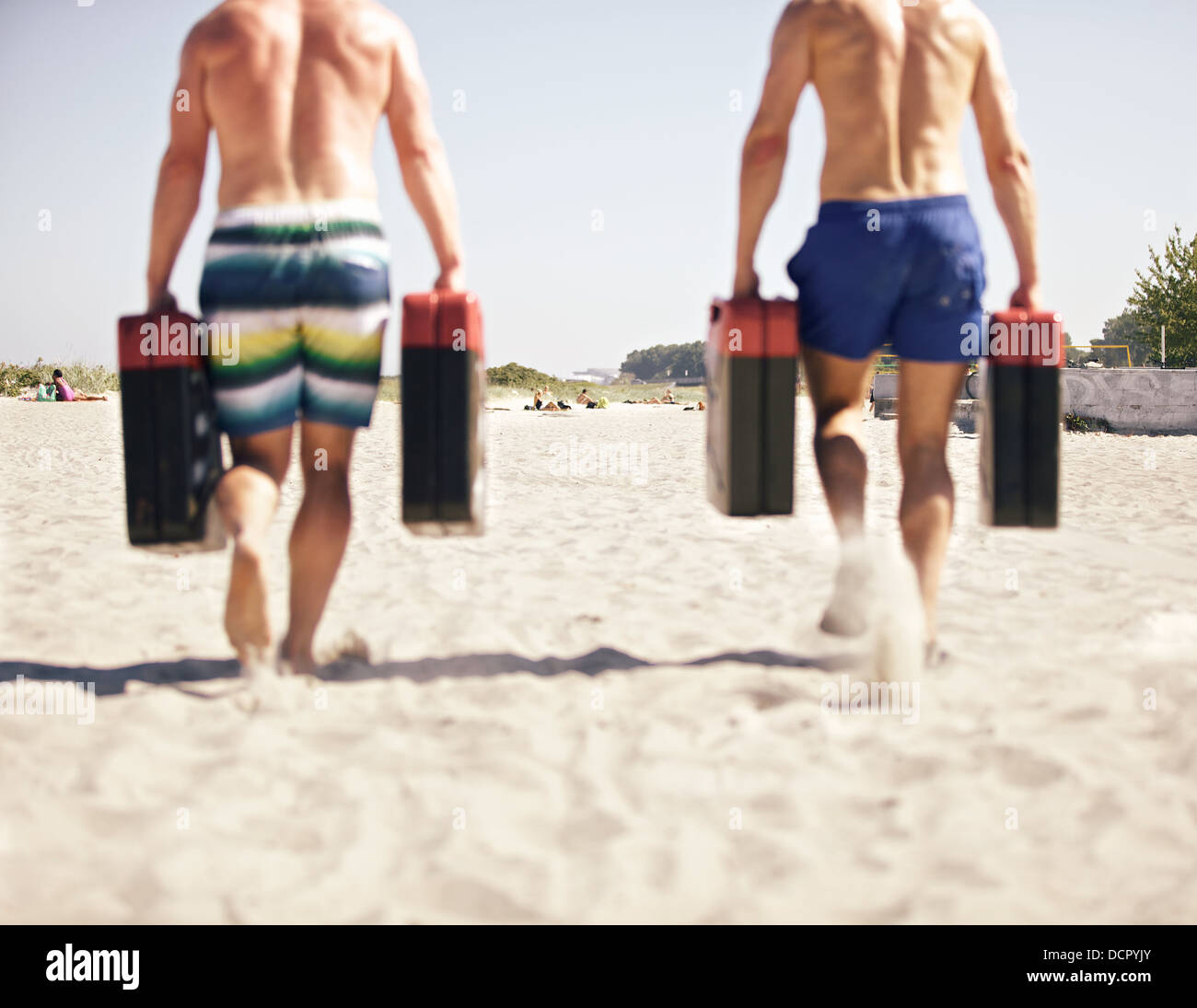 Two men running with jerry cans as a part of crossfit games - Stock Image
