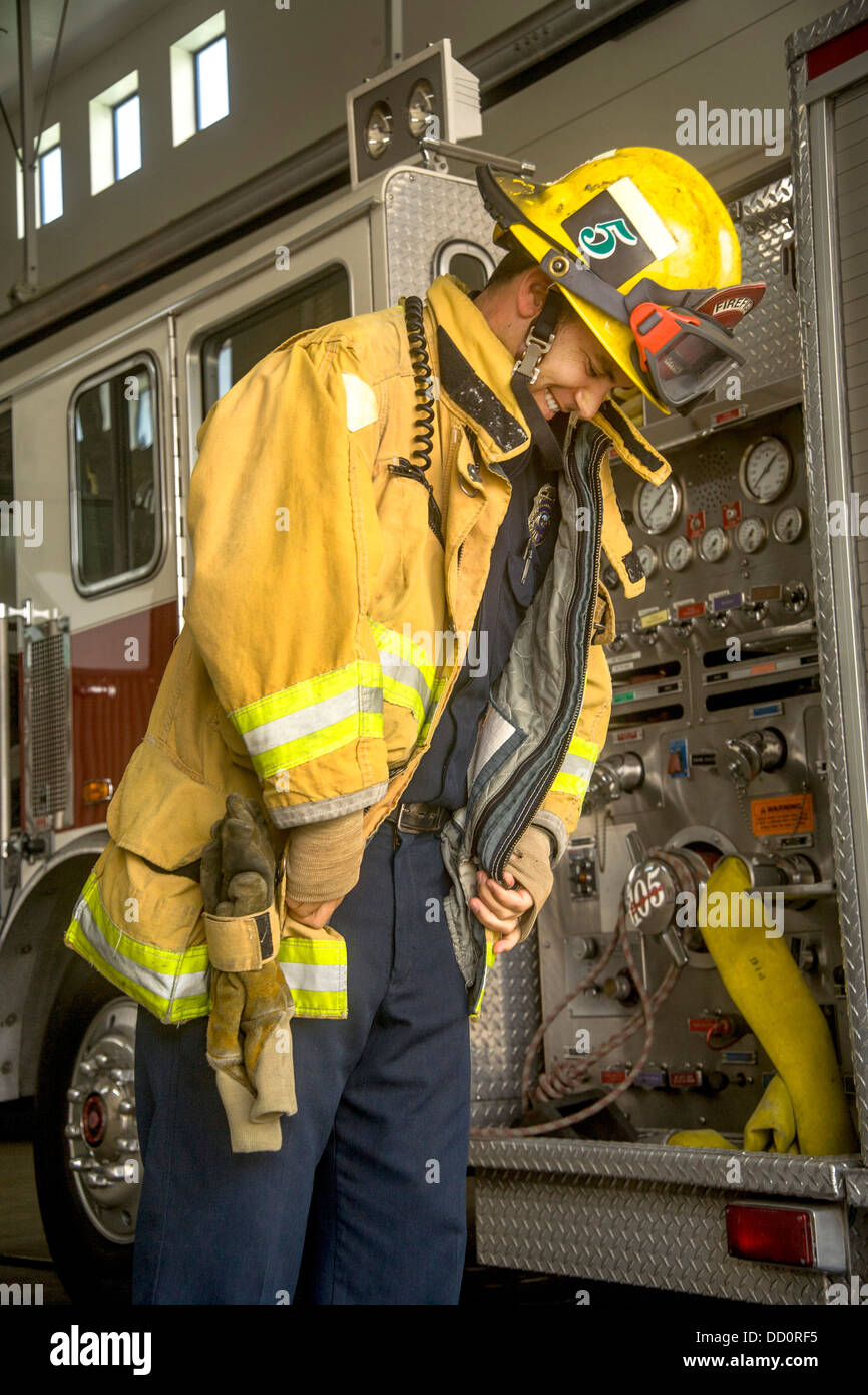 Wearing his helmet, a young firefighter dons his yellow safety jacket at a firehouse in Laguna Niguel - Stock Image
