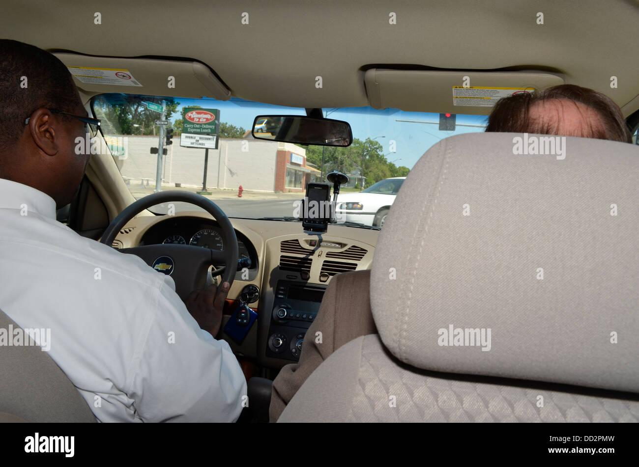 Two male parole officers in vehicle on their way to meet a parolee at his place of work. - Stock Image