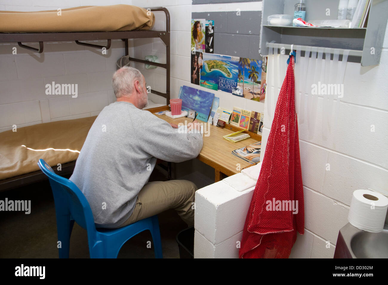 Inmate alone in cell writing a letter. Work release, minimum security prison, Lincoln, Nebraska, USA. - Stock Image