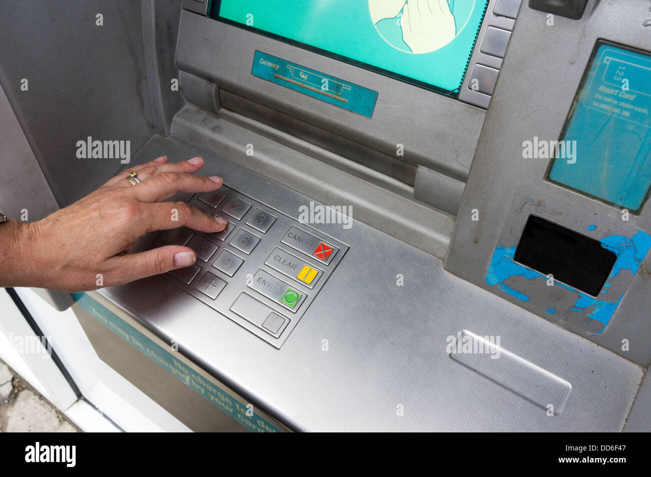 A woman entering her PIN number at a bank cash machine. Stock Photo