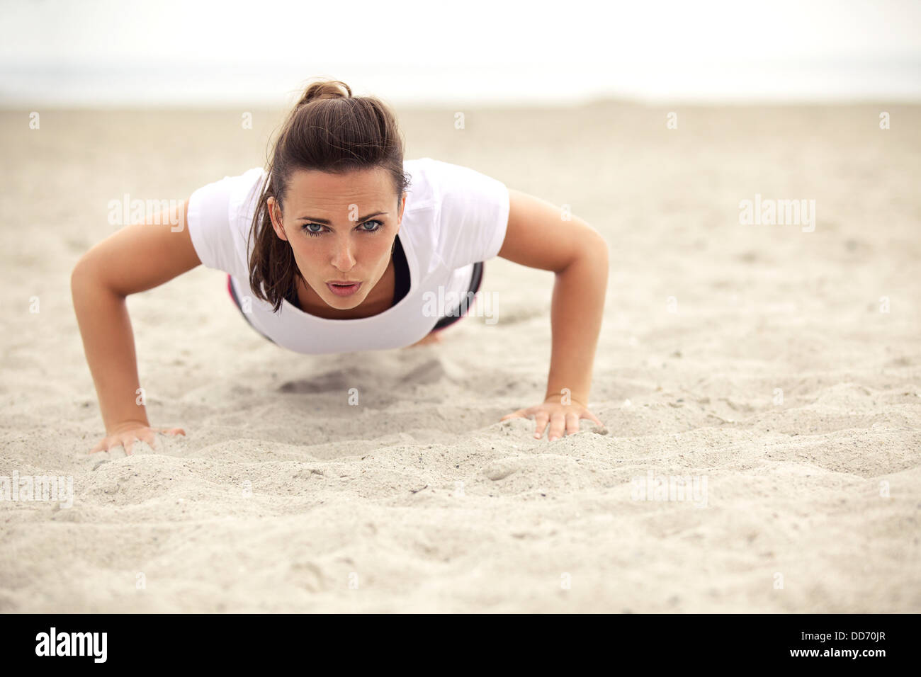 Fitness woman on the beach doing push up exercise - Stock Image