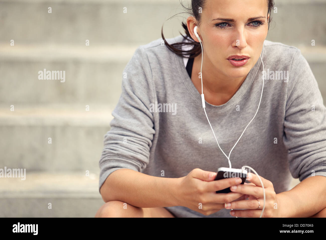 Serious female athlete listening to mp3 music during her break - Stock Image