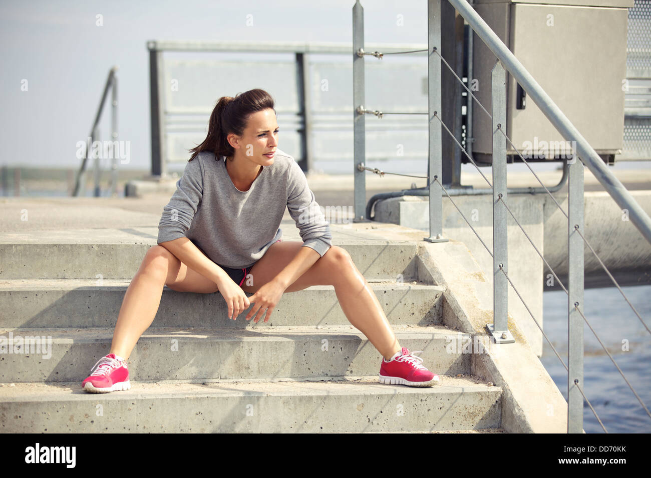Female athlete sitting on the stairs taking a break from running - Stock Image