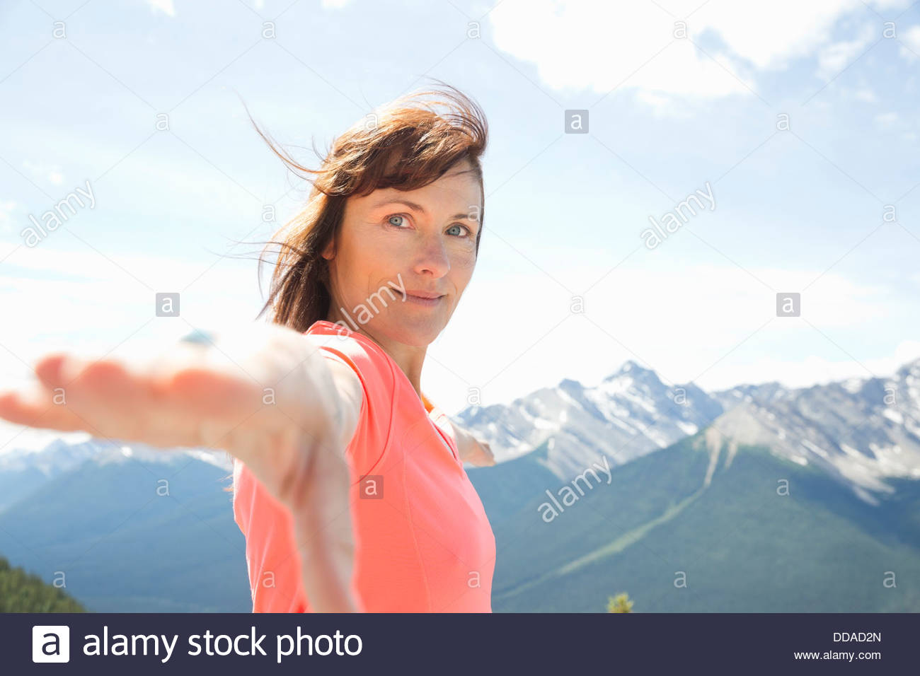 Mature woman practicing yoga on mountaintop - Stock Image