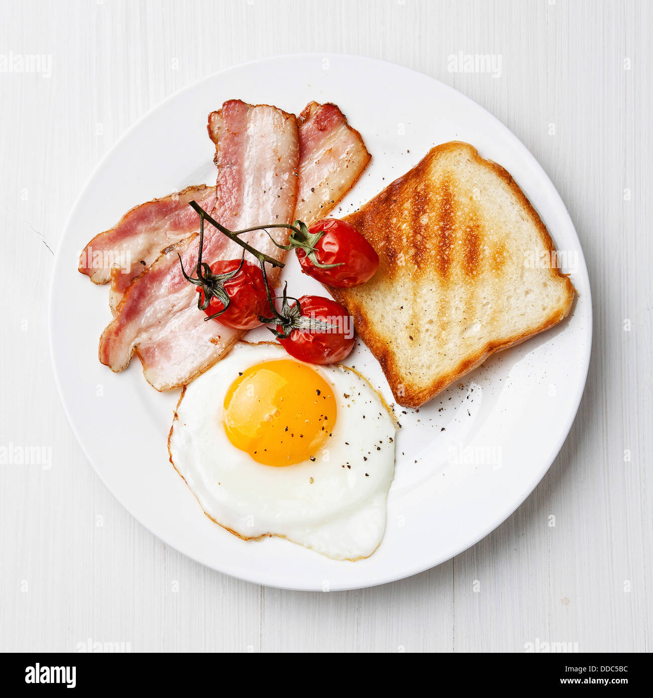 Breakfast with Fried egg and bacon on plate - Stock Image