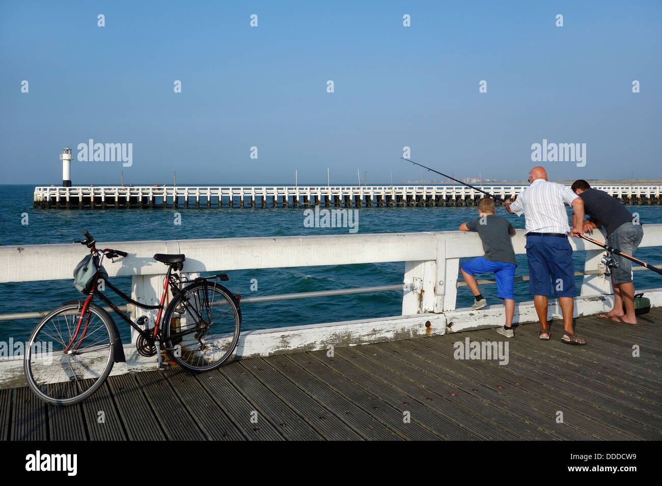 Son, father and grandfather angling with fishing rod from pier along the North Sea coast at Nieuwpoort / Nieuport, - Stock Image