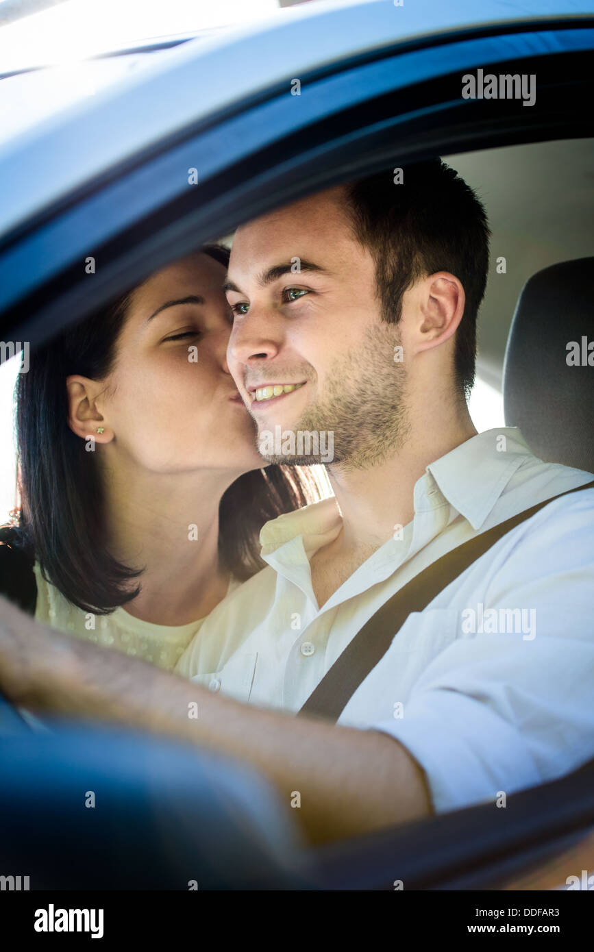 Couple in car - young woman kissing man in car while driving - Stock Image