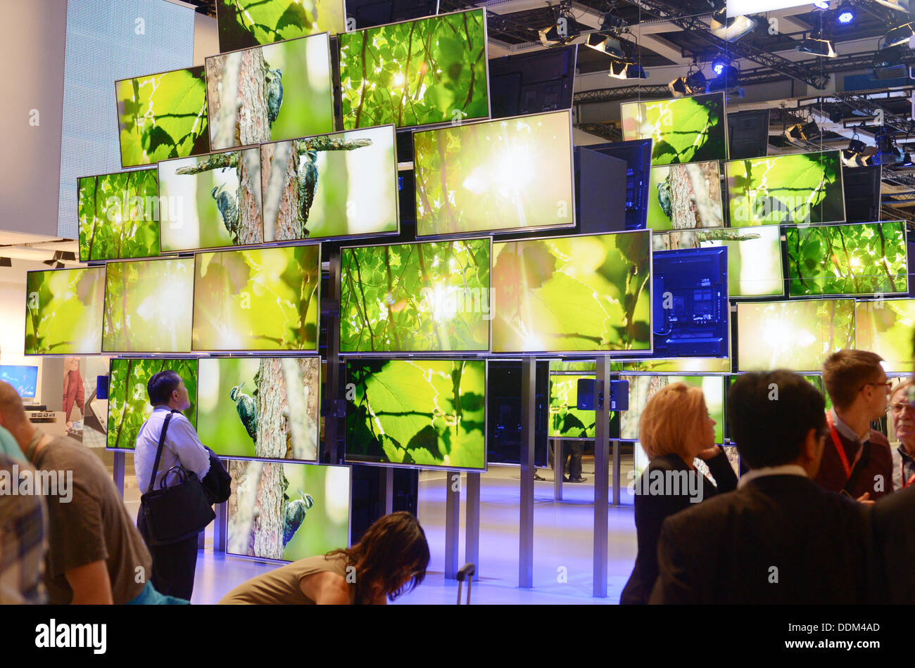Berlin, Germany. 4th Sep, 2013. Visitors stand in front of a wall of 4K televisions at the fair stand of electronics - Stock Image