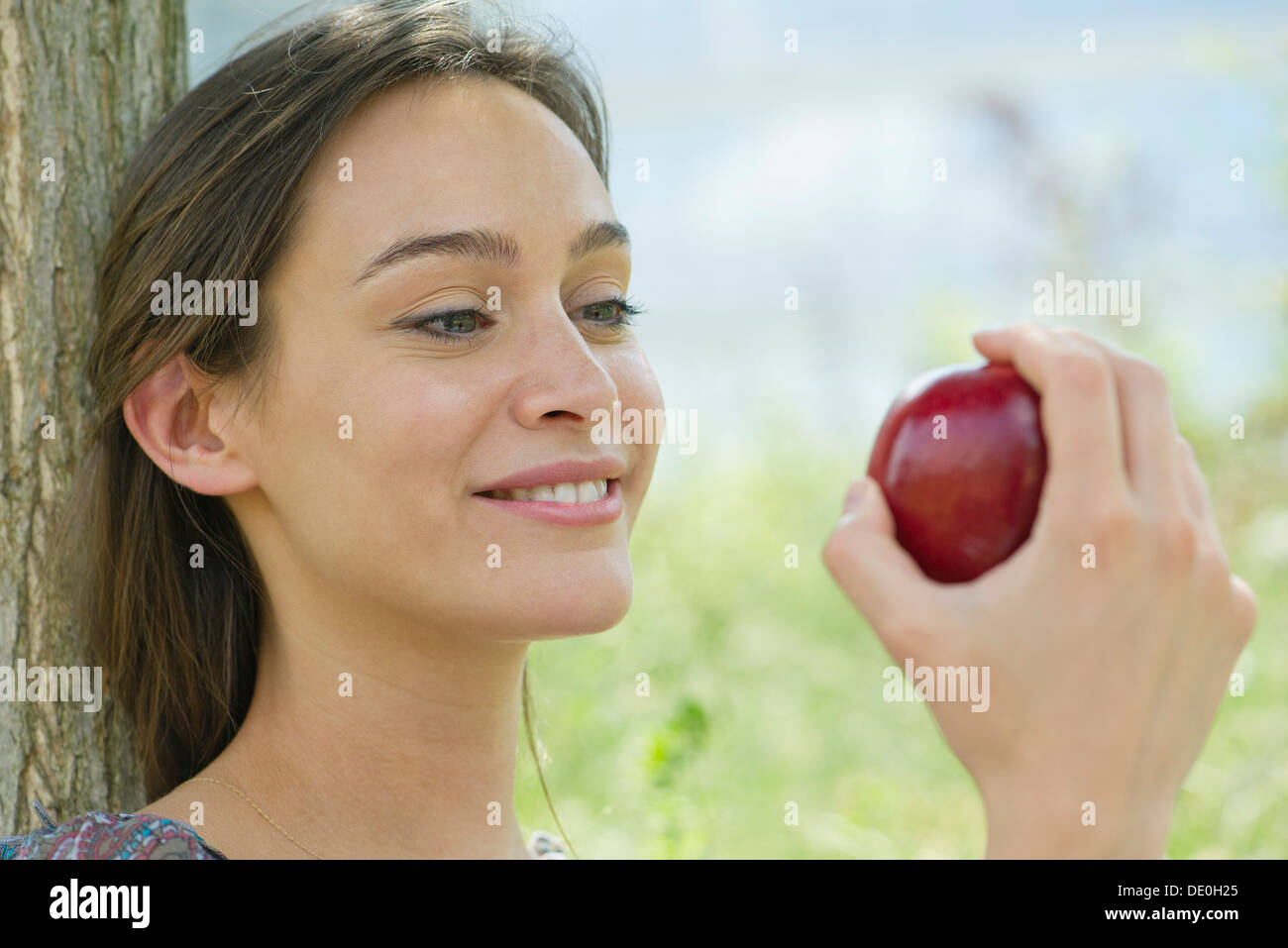 Woman sitting outdoors with apple - Stock Image