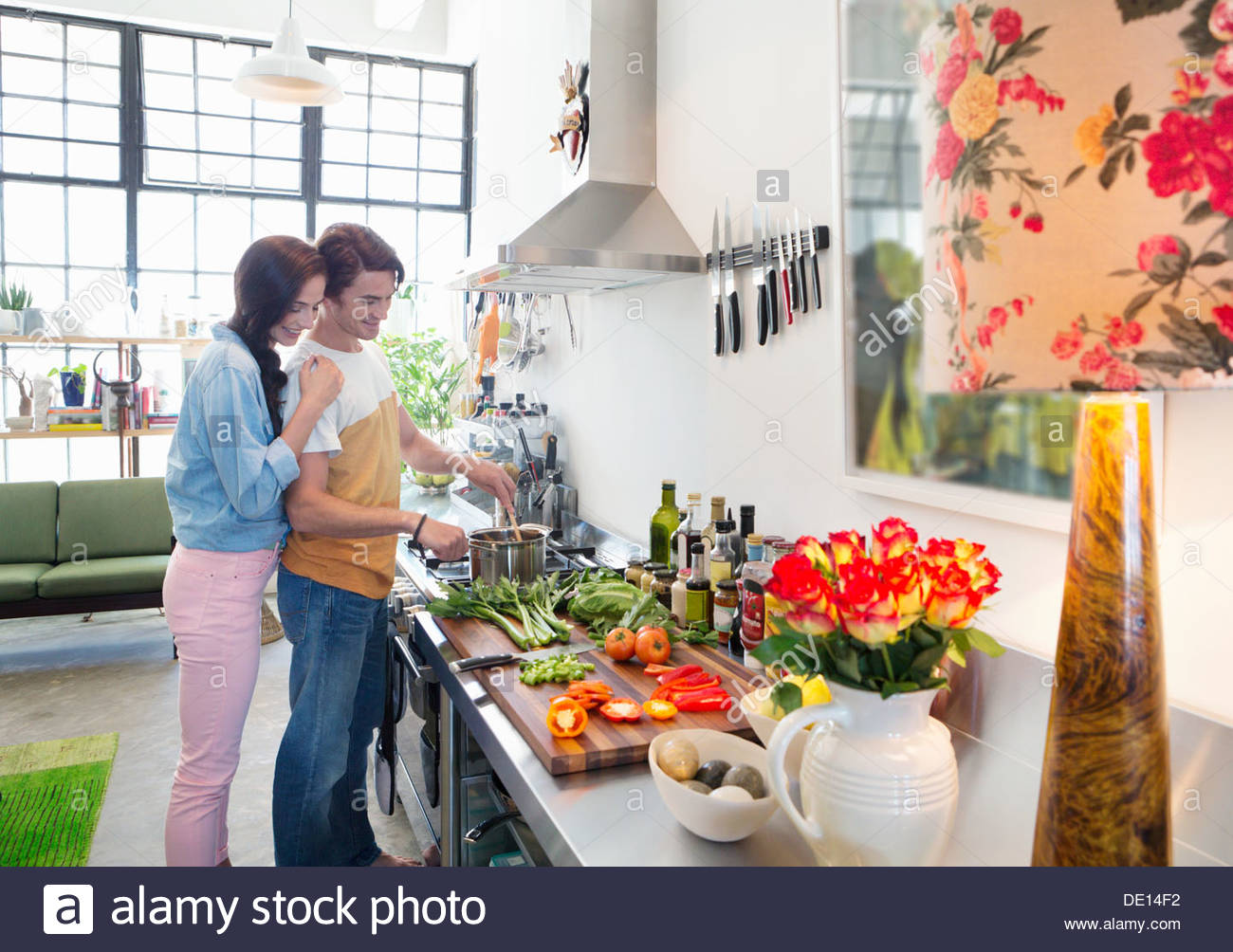 Couple cooking at stove in kitchen - Stock Image