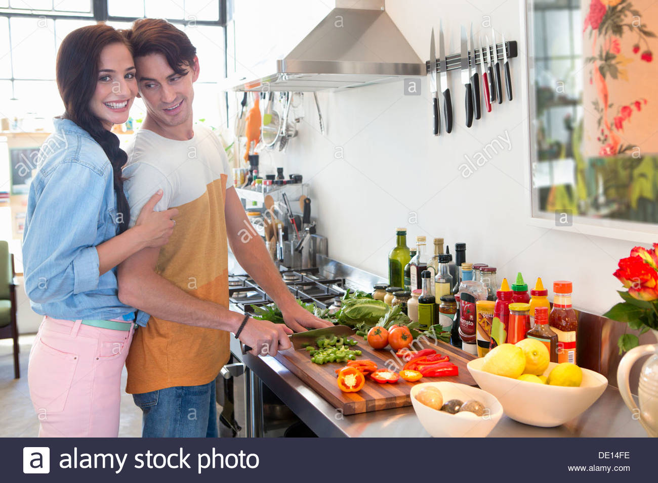Portrait of smiling couple cooking in kitchen - Stock Image