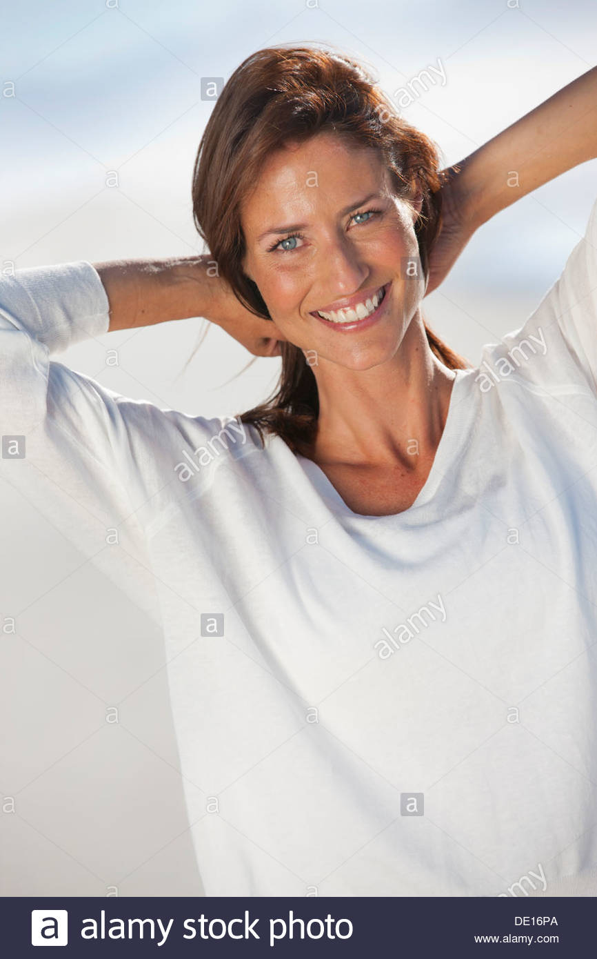 Portrait of smiling woman with hands behind head on beach - Stock Image