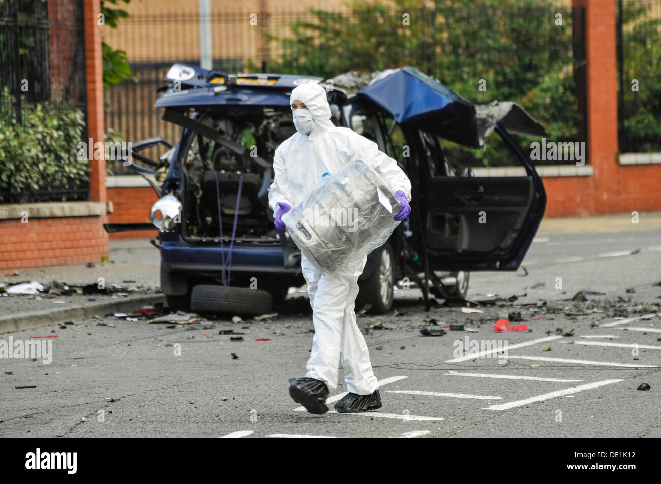 Belfast, Northern Ireland. 10th September 2013 - A PSNI forensics officer carries away the beer keg which was in - Stock Image
