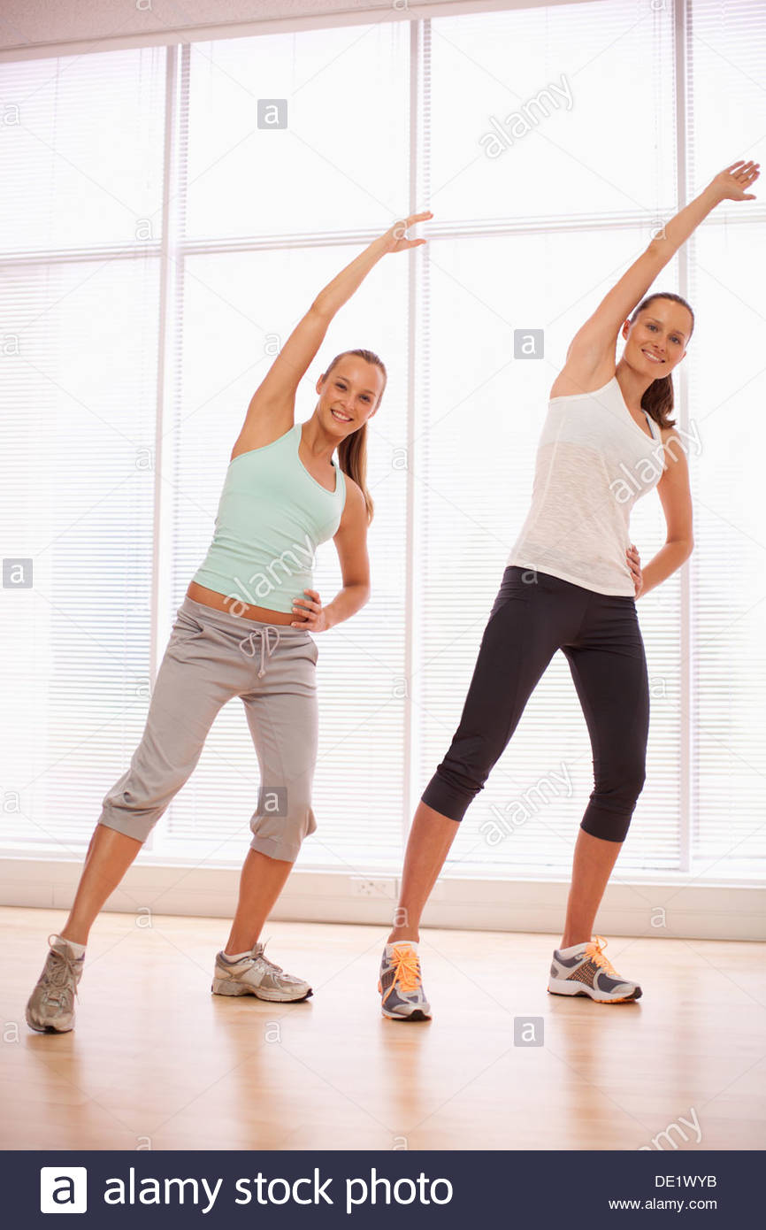 Smiling women with arms raised in exercise class - Stock Image