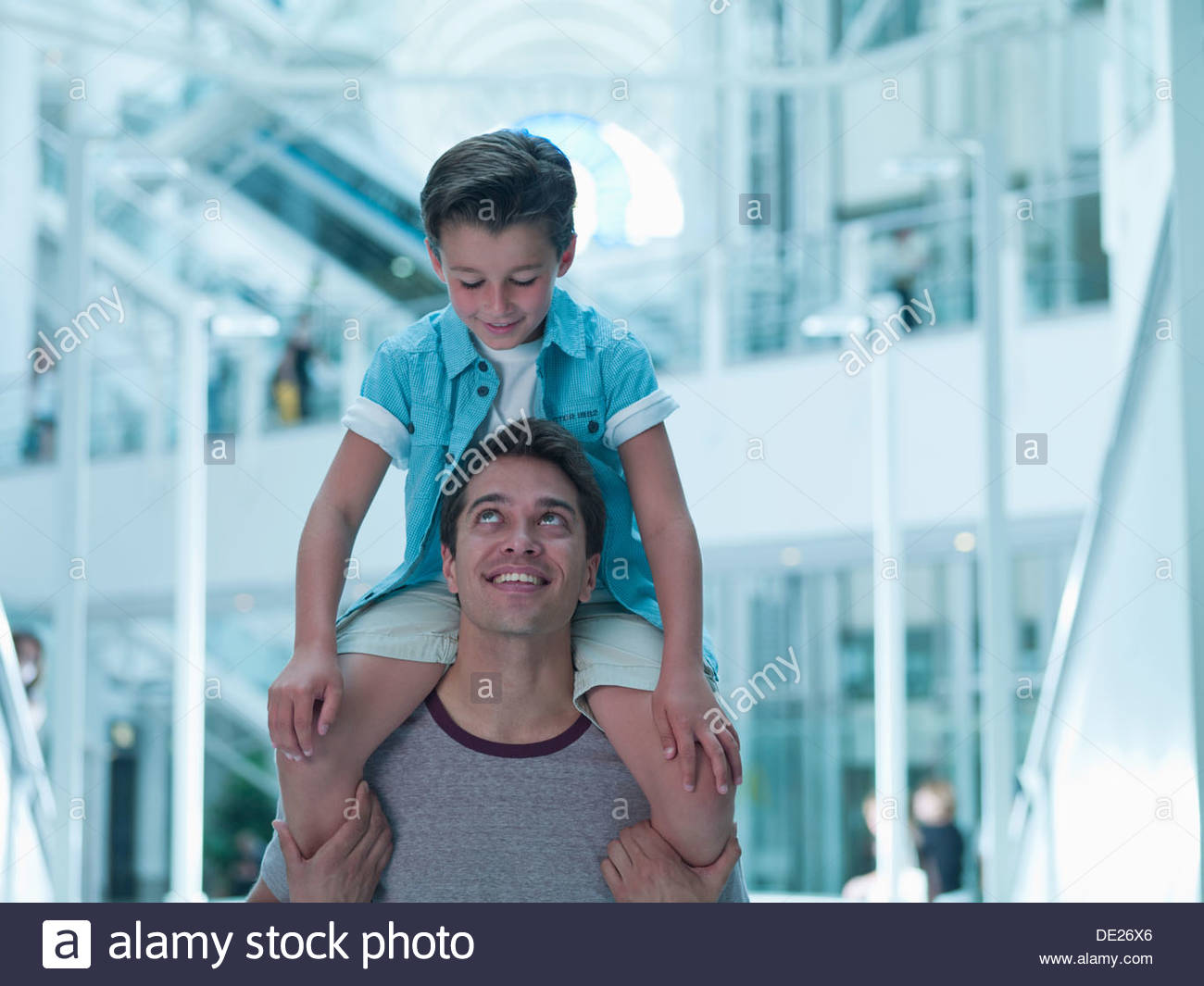 Father carrying son on shoulders in mall - Stock Image