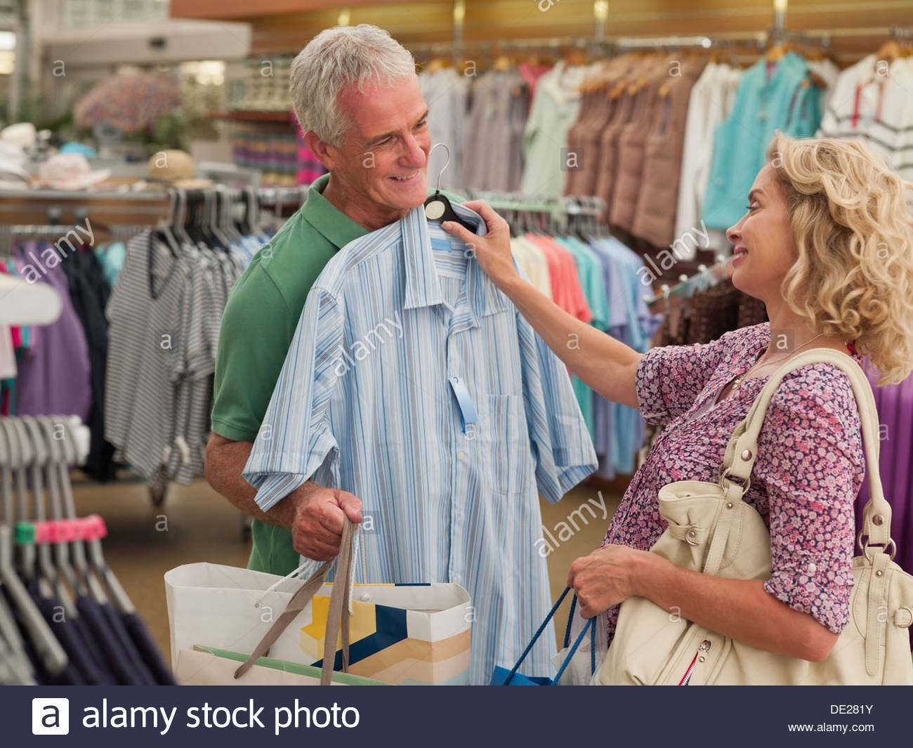 Couple shopping for clothing in store - Stock Image