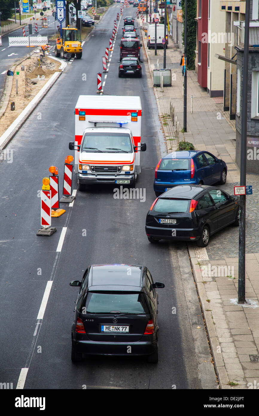 Ambulance for a trip alarm with flashing lights and sirens. Moves to an inner-city site against the direction of traffic. - Stock Image