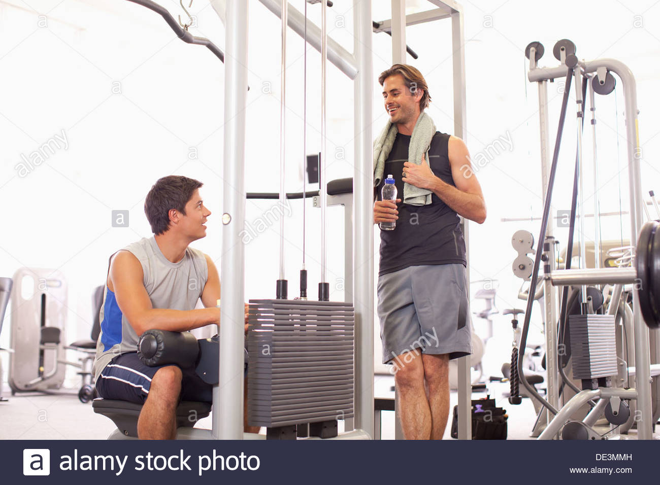 Portrait of smiling men working out in gymnasium - Stock Image