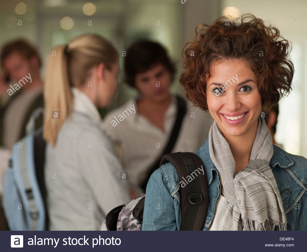 Female college student smiling in classroom - Stock Image