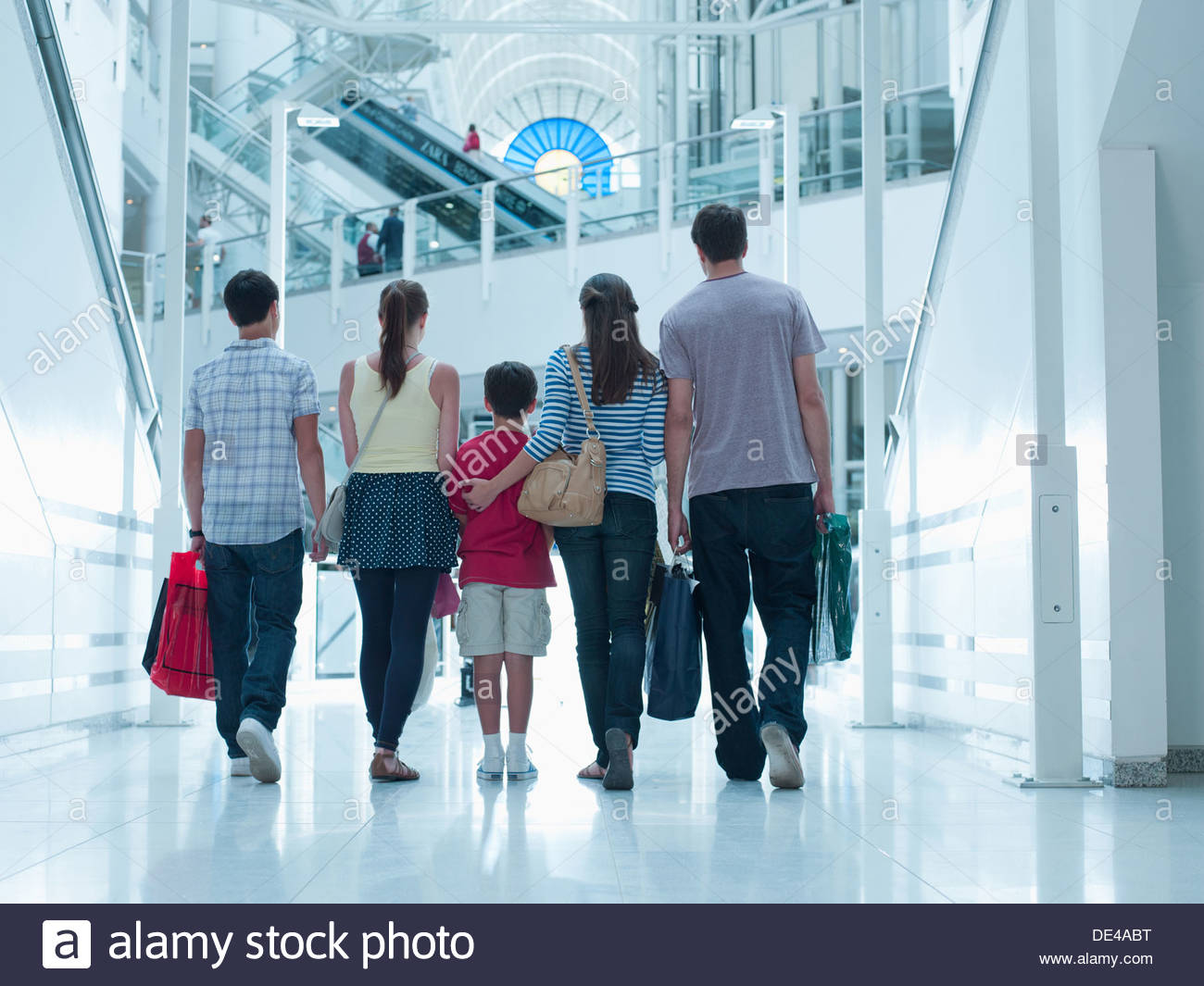 Family carrying shopping bags in mall - Stock Image