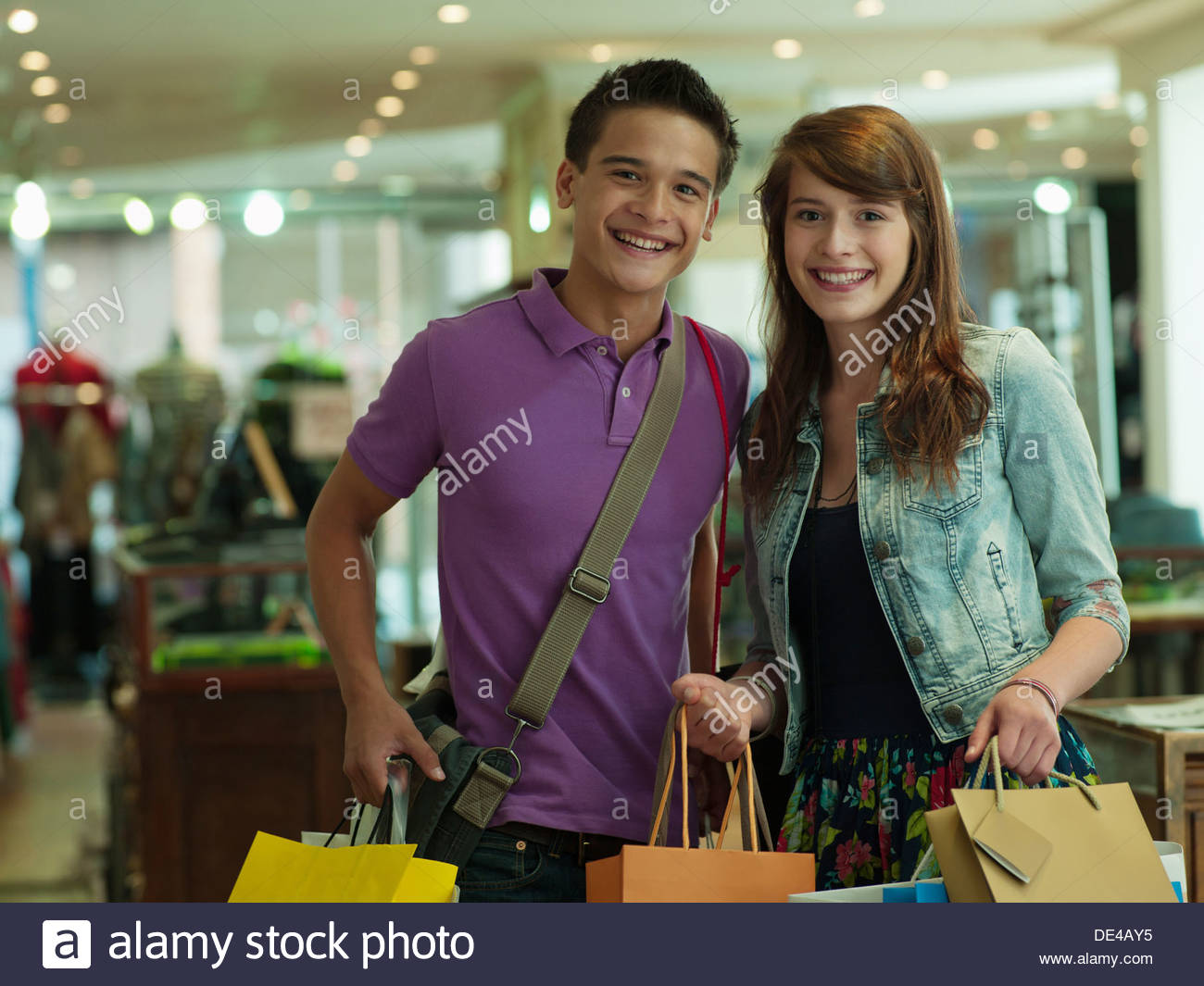 Smiling couple carrying shopping bags in store - Stock Image