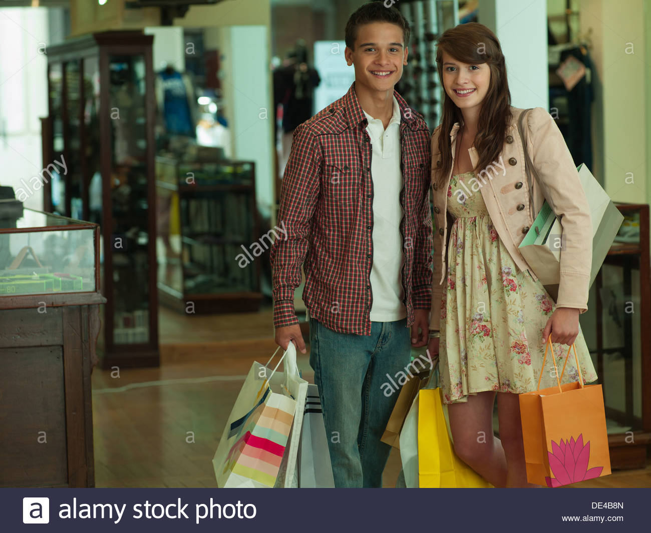 Smiling couple carrying shopping bags in clothing store - Stock Image