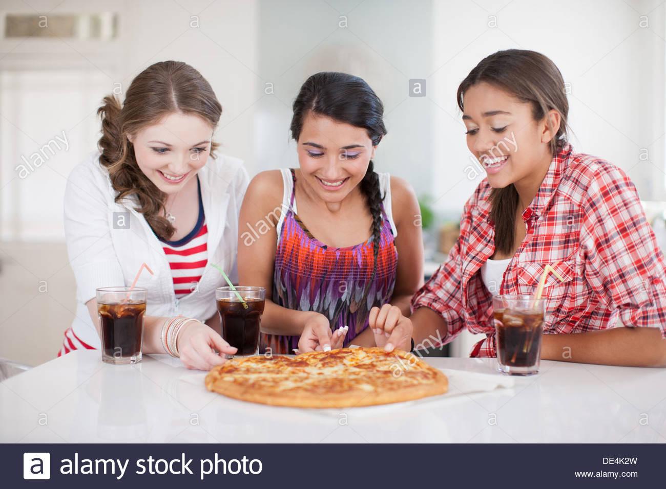 Teenage girls eating pizza - Stock Image