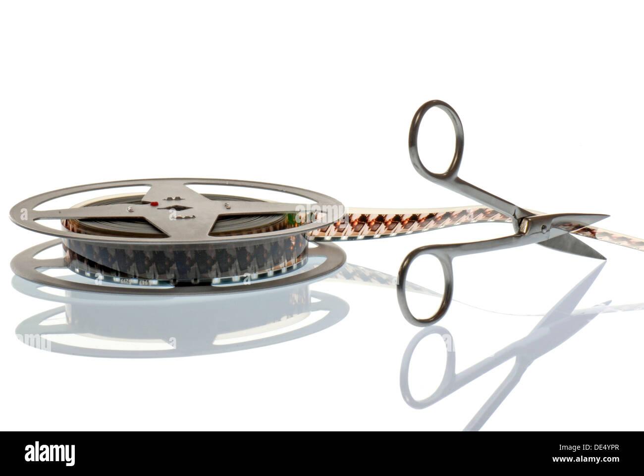 Film reel with scissors, symbolic image for film editing - Stock Image