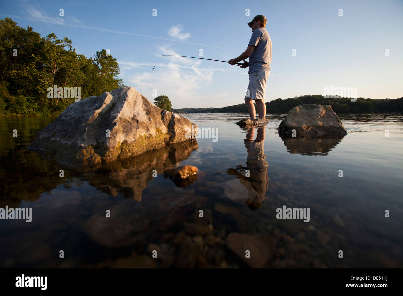 A man casts his line while fishing on Lake Windsor in Bella Vista, Arkansas. - Stock Image