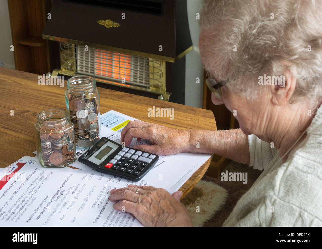 Elderly lady in her nineties looking at gas and electric bills with calculator and jars of coins on table. Gas fire Stock Photo