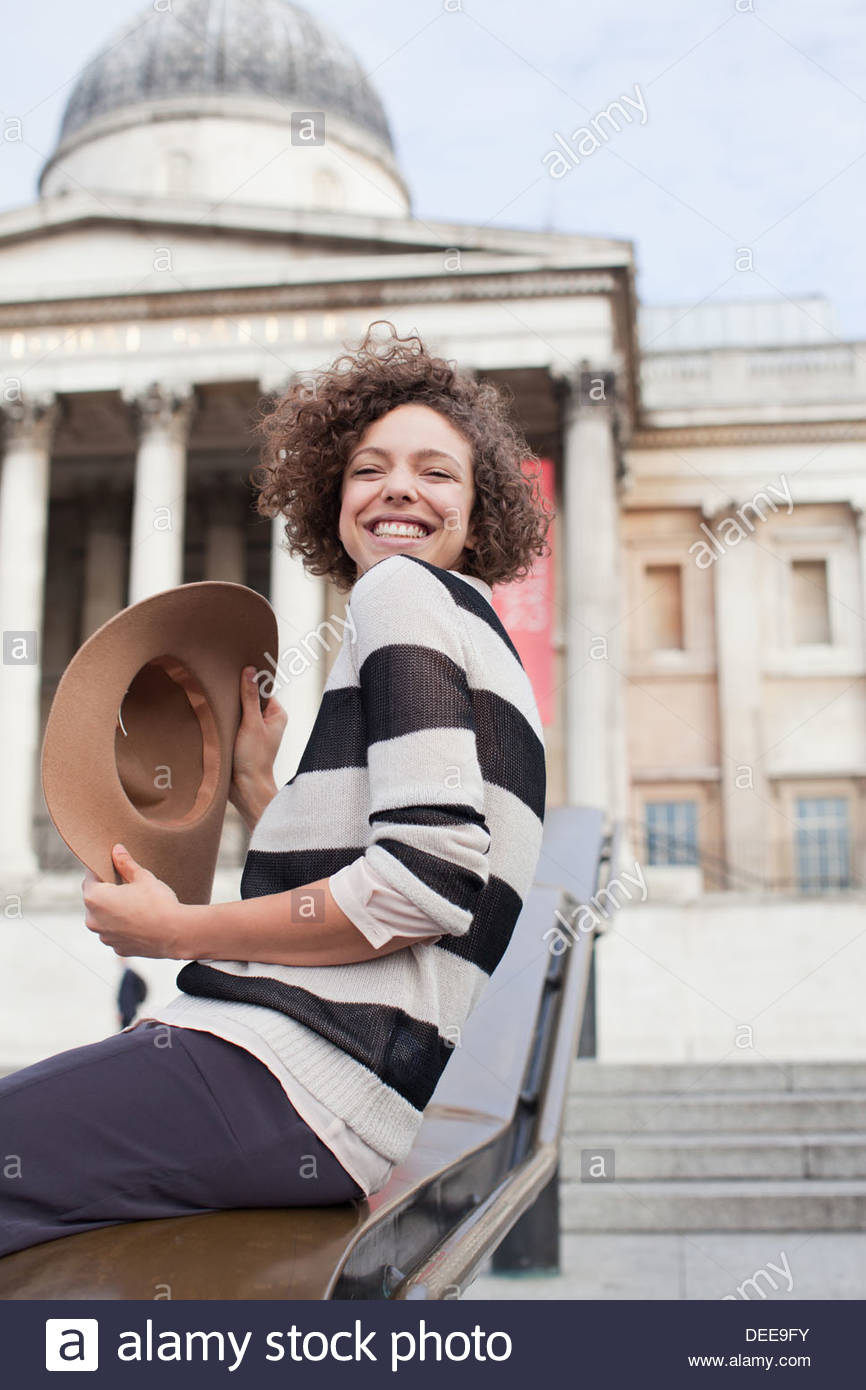 Exuberant woman with hat below historical landmark in London - Stock Image