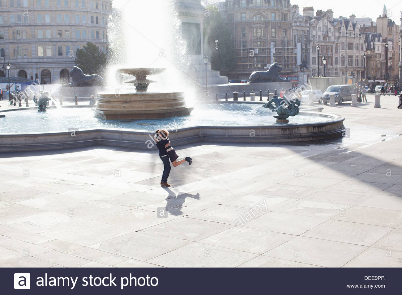 Man lifting woman in front of urban fountain - Stock Image