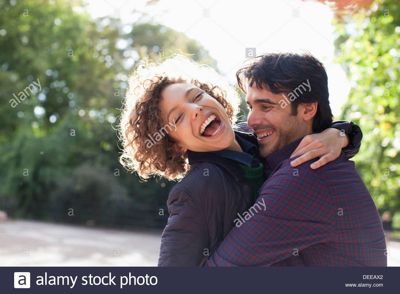 Sun shining behind happy couple hugging - Stock Image