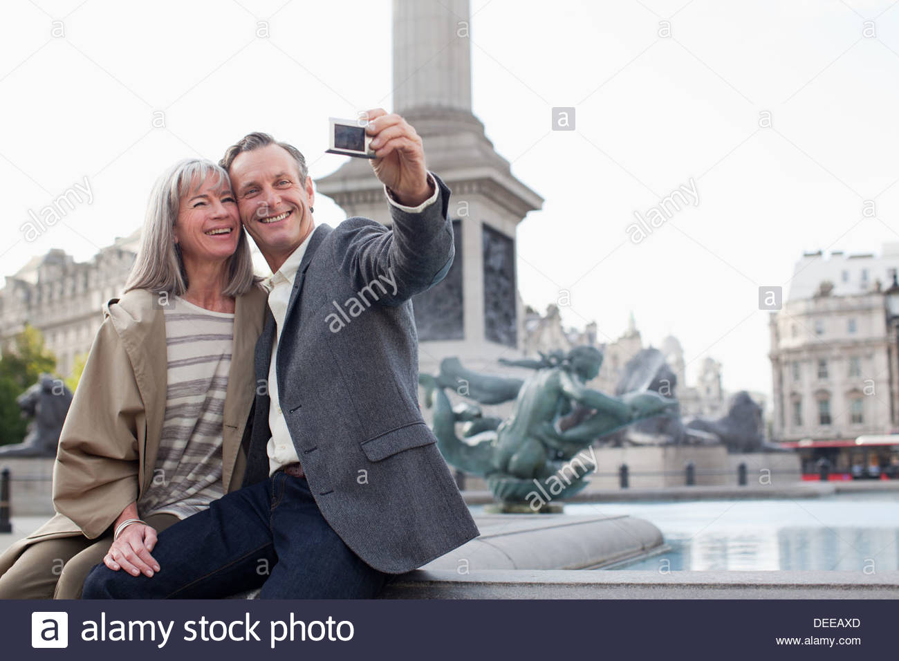 Couple taking self-portrait with digital camera under monument - Stock Image