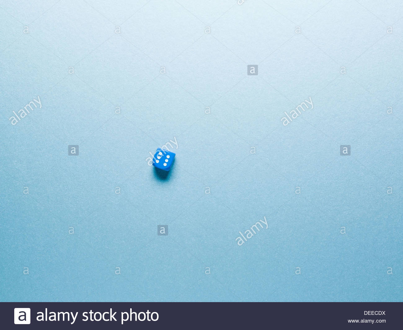 blue dice on surface - Stock Image