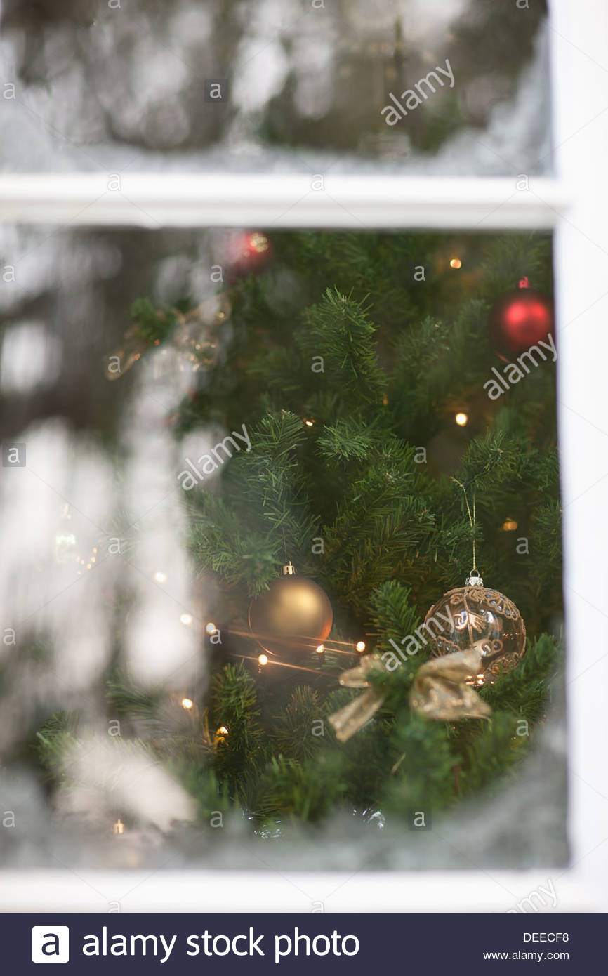 Christmas ornaments on tree behind window - Stock Image