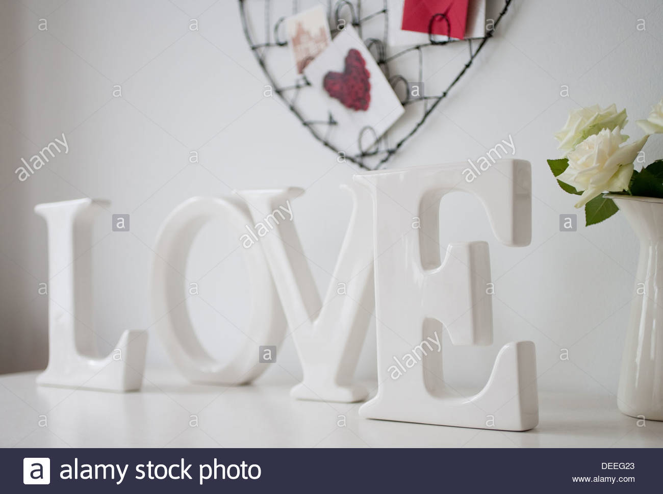 Wooden 'love' letters decoration, roses on desk - Stock Image