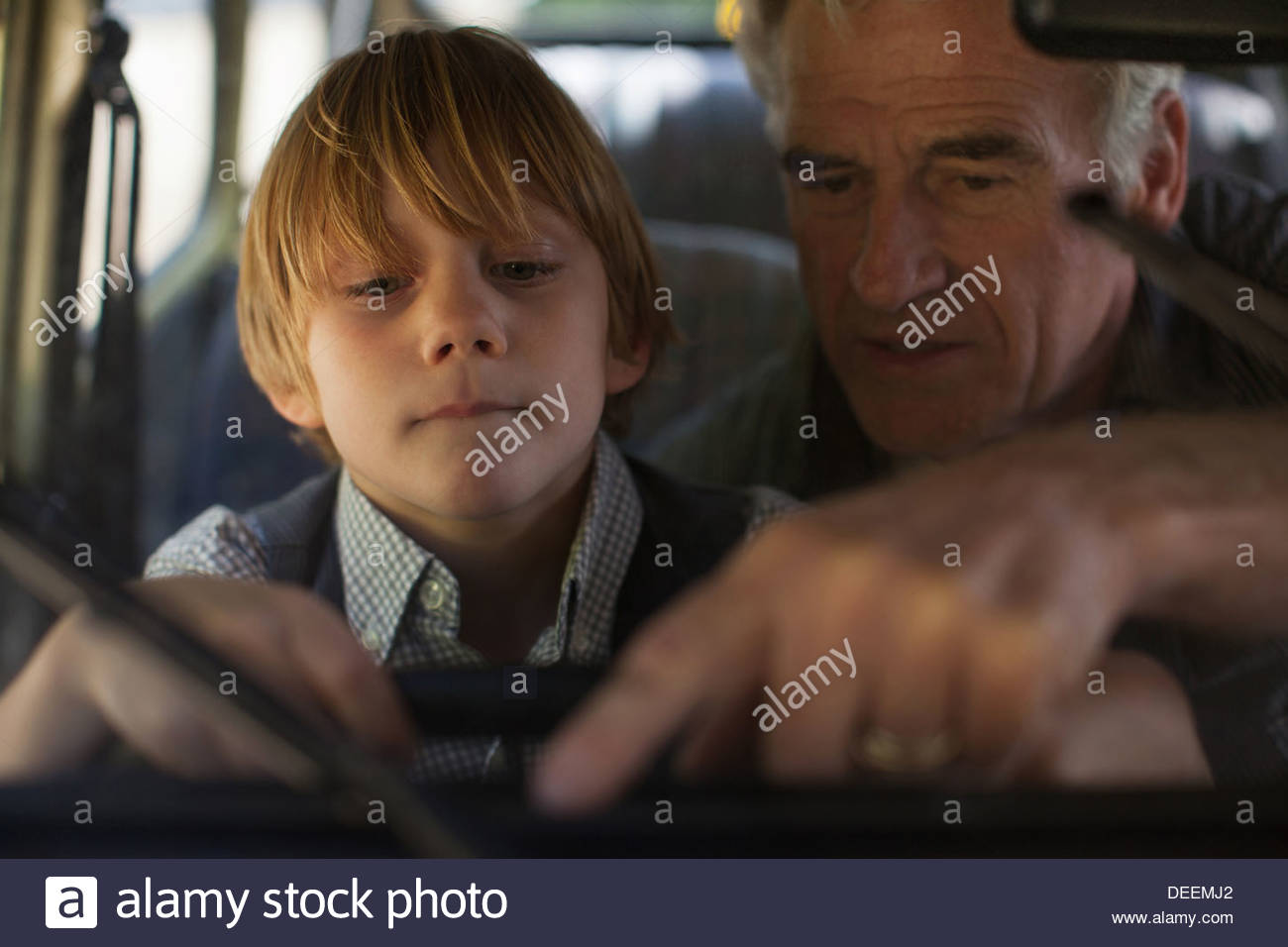 Grandfather and grandson behind steering wheel - Stock Image