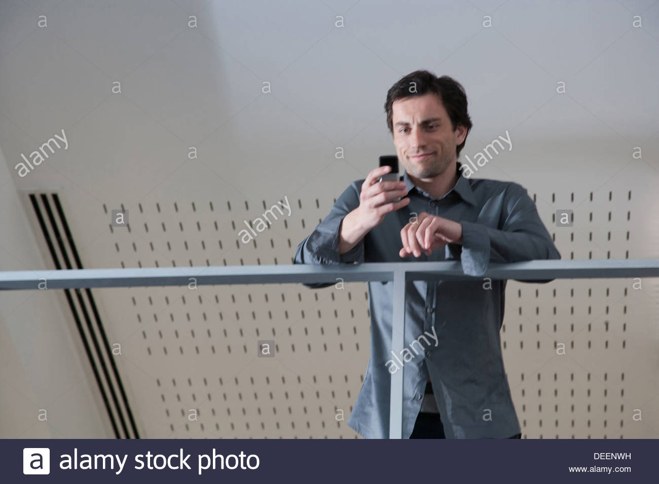 Businessman leaning on rail with using cell phone in office - Stock Image