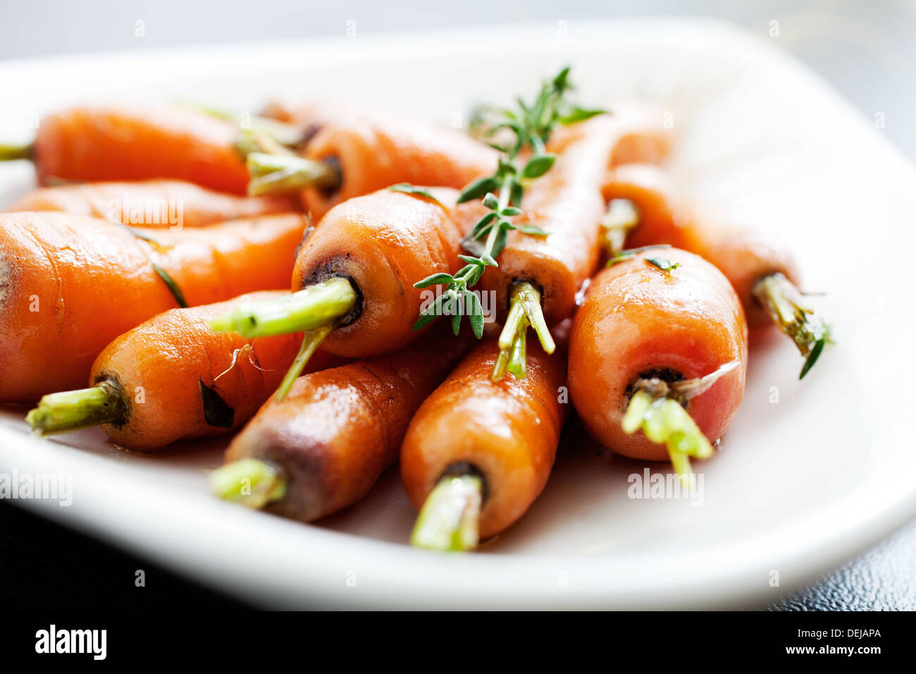 Close up of carrots with fresh thyme  - Stock Image