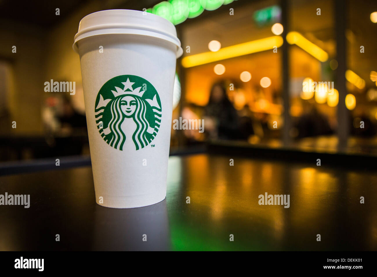 A Starbucks coffee cup sitting on a table outside Starbucks coffee shop, Canary Wharf. London, UK. Stock Photo