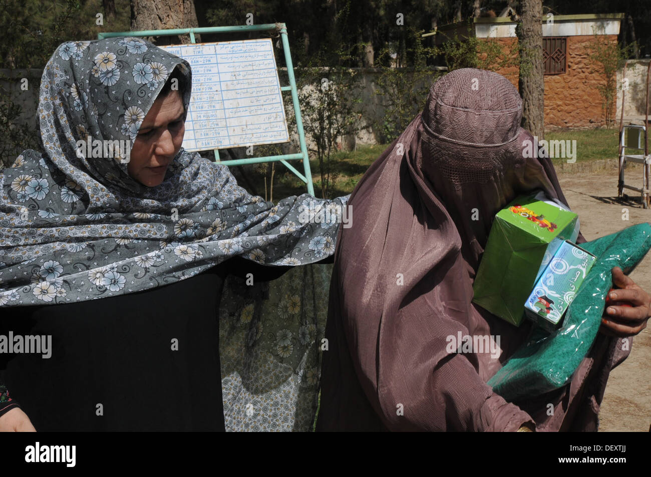 Sadiqa Jalali, directorate of women affairs, passes out humanitarian aide items after a women's shura in Tarnek - Stock Image