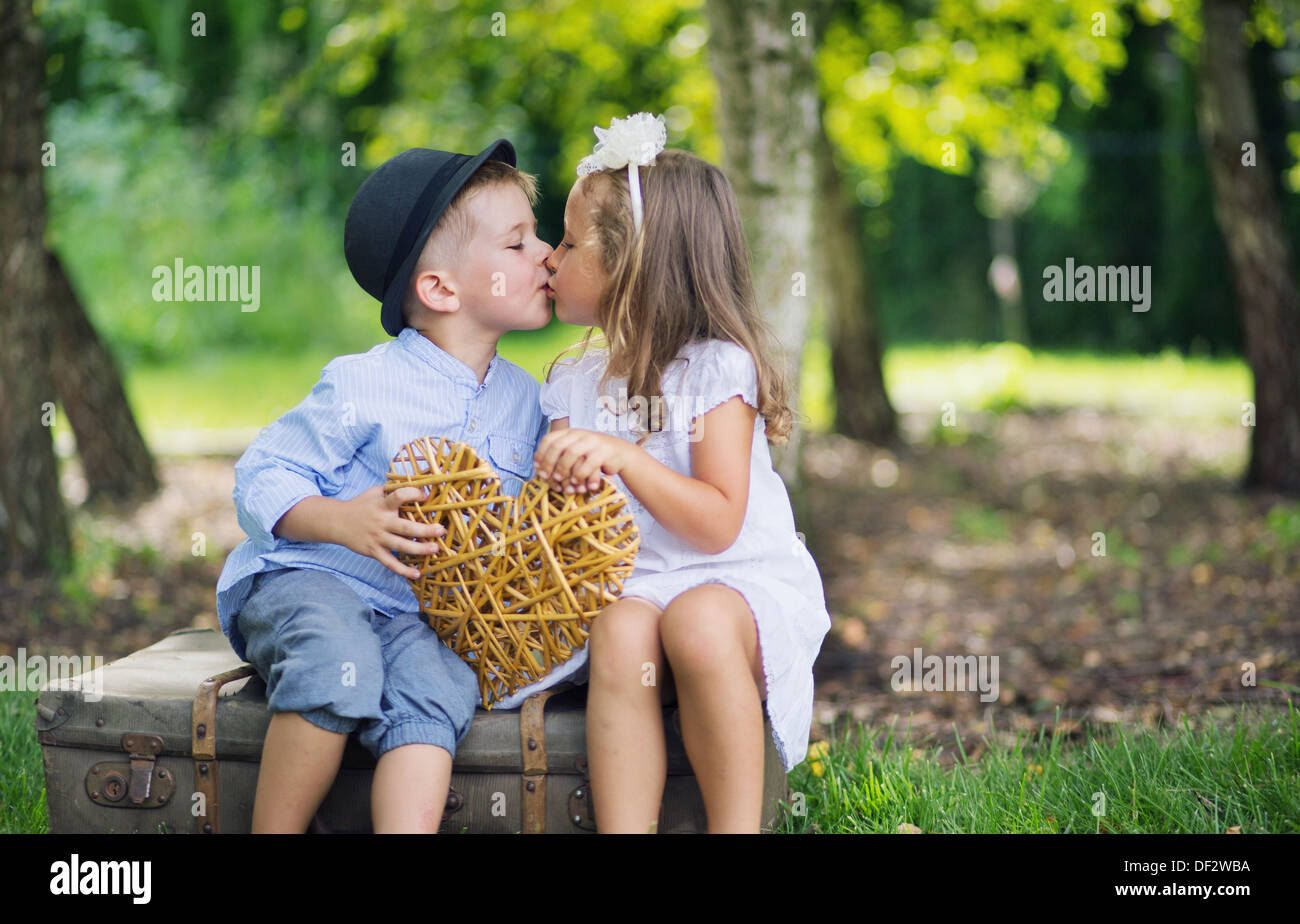 fine picture of two cute children kissing each other stock photo