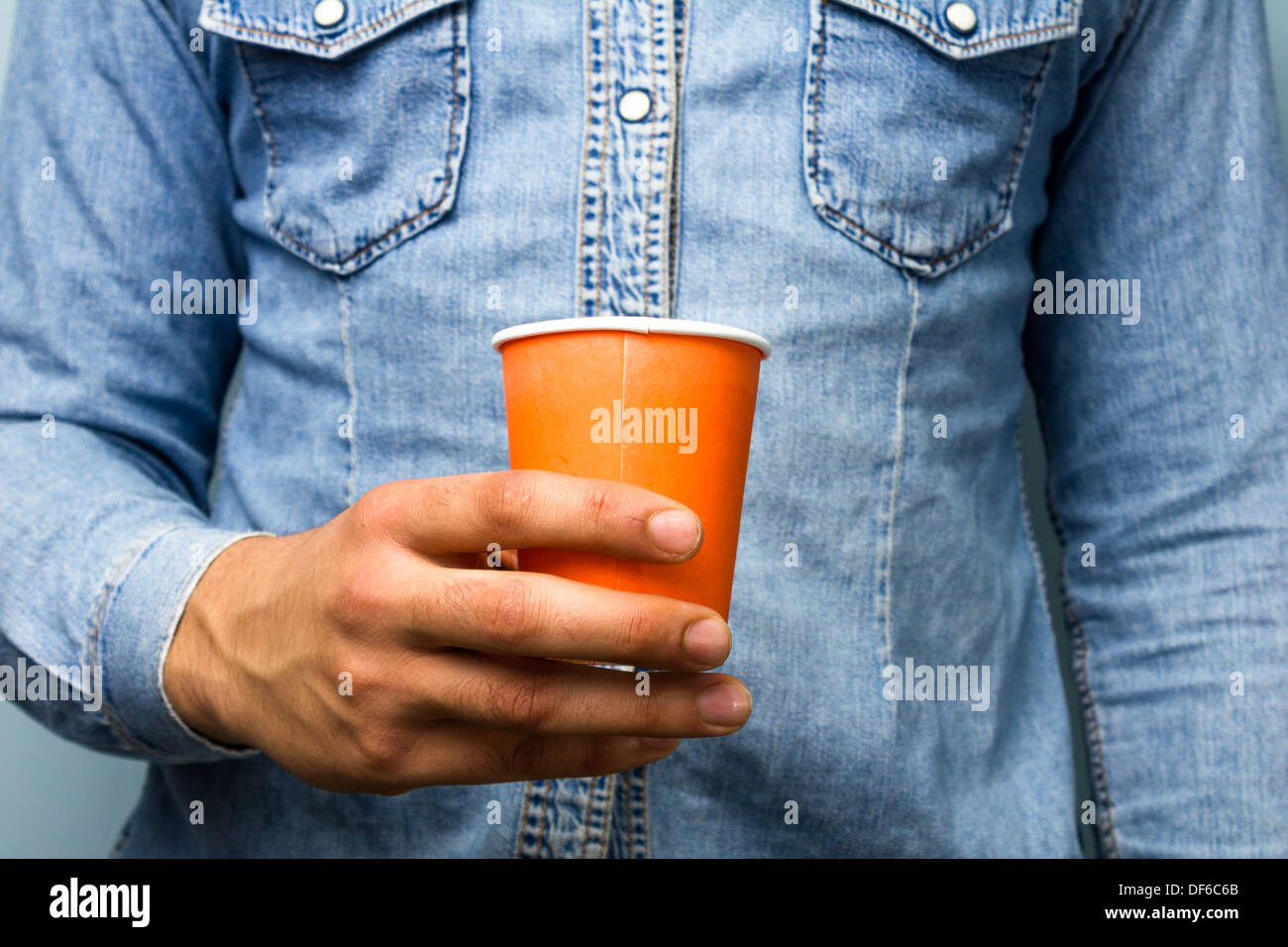 Close up on man in blue denim shirt holding an orange paper cup - Stock Image