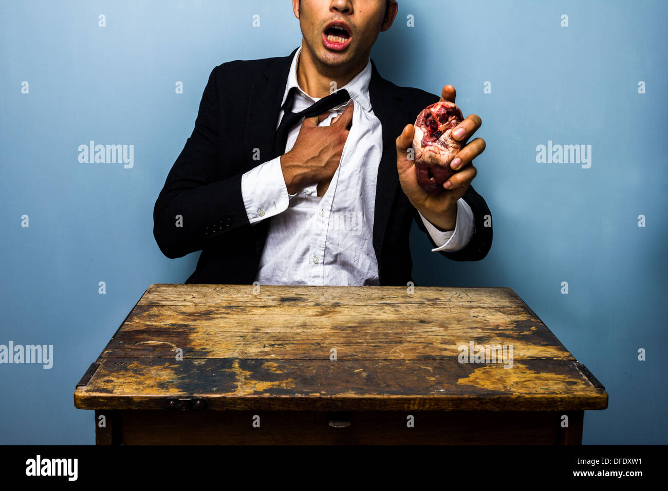 Young businessman is holding his chest in pain whilst holding a raw animal's heart in his other hand to symbolize - Stock Image