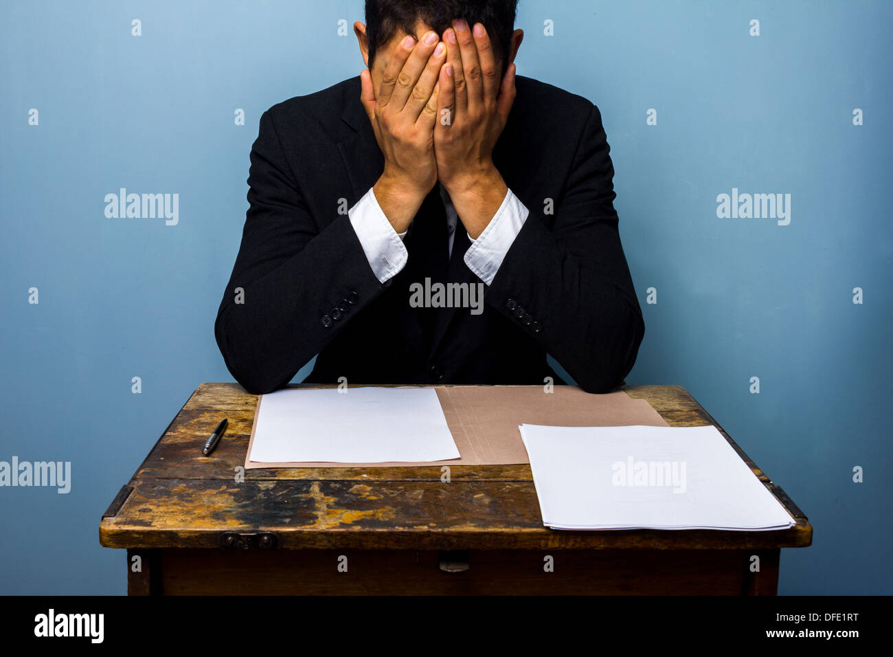 Tired and frustrated businessman with important documents - Stock Image